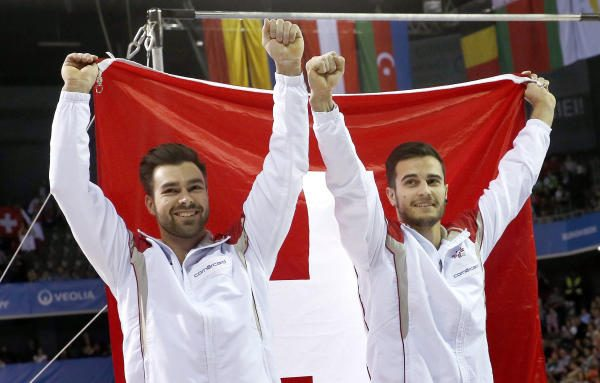 epa05923518 Winner Pablo Braegger (R) and second placed Oliver Hegi of Switzerland (L) celebrate with their national flag after the high bar final during 2017 Artistic Gymnastics European Championships, at  the Polivalenta Sports Hall in Cluj-Napoca, Romania, 23 April 2017.  EPA/ROBERT GHEMENT